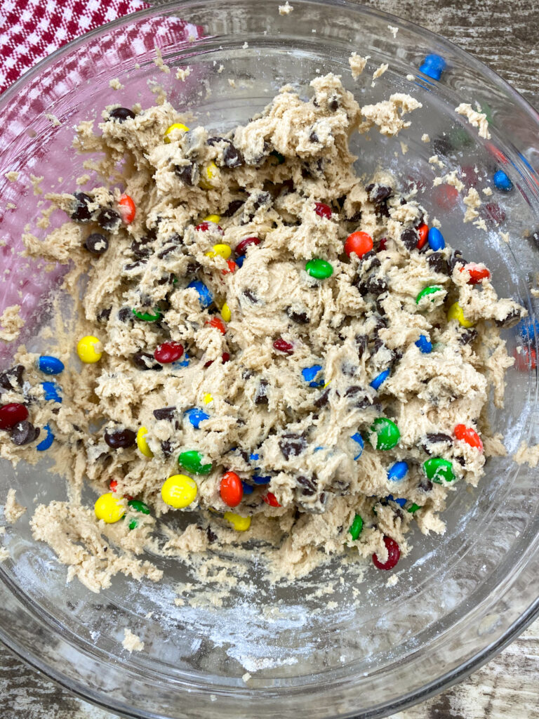 M and m cookie dough in a glass bowl.