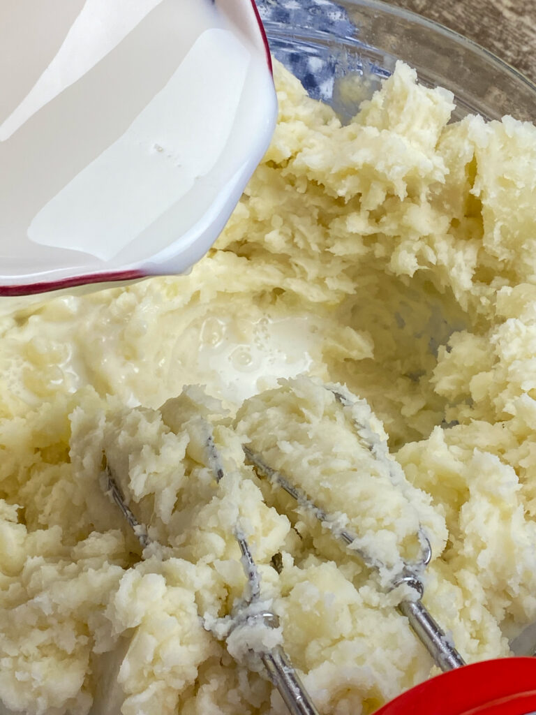 Pouring milk into mashed potatoes.