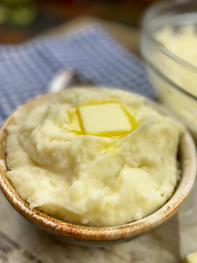 Mashed potatoes in a small bowl with butter.