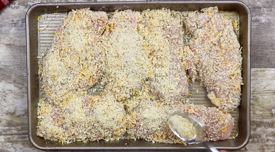 Breaded chicken on a cookie sheet.
