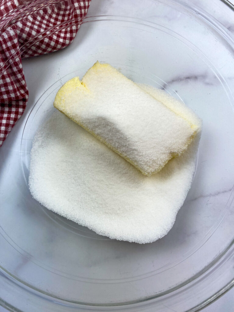Butter and sugar in a glass bowl.
