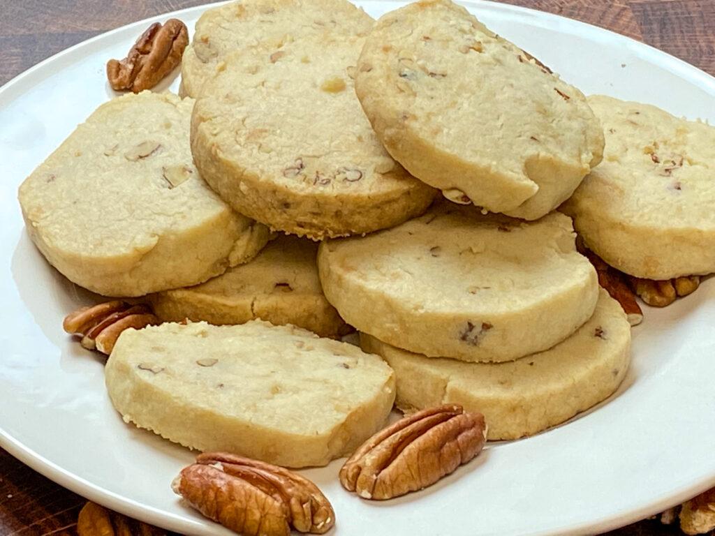 Shortbread pecan sandies sitting on a white plate.