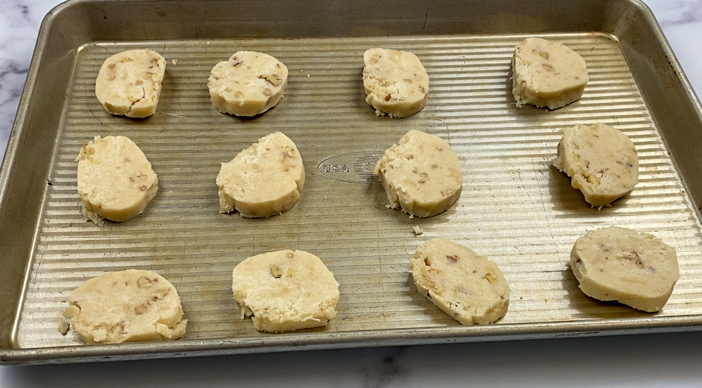 Cookies sliced and on a cookie sheet.