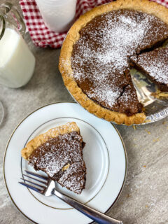 Chocolate chess pie sliced and on a white plate.