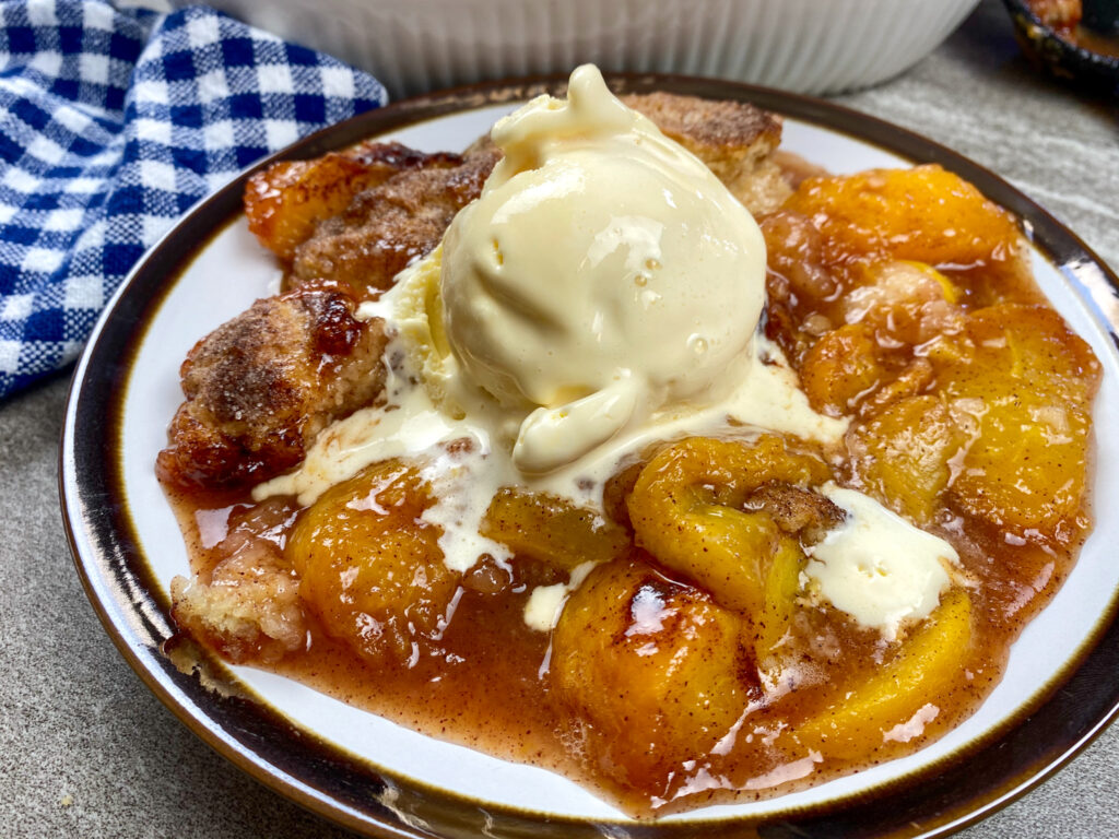 peach cobbler on a plate with ice cream.