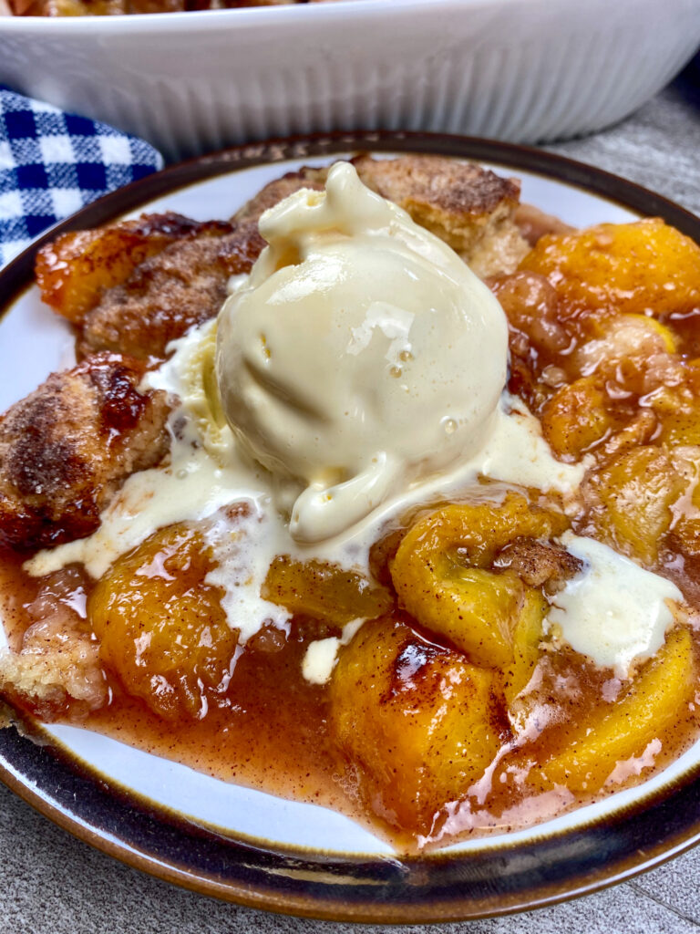 Peach cobbler on a round plate with ice cream on top.