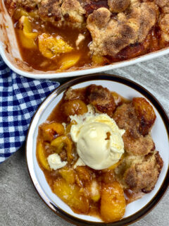 Peach cobbler with ice cream on a plate.