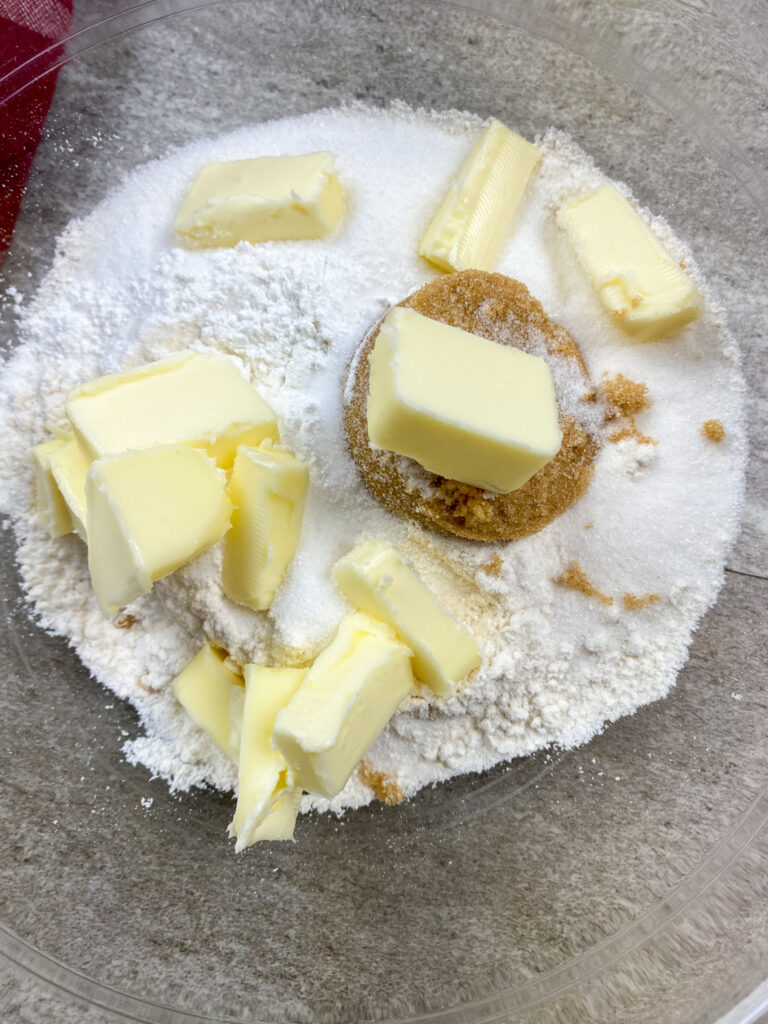 Cubes of butter in a glass bowl with sugar and flour.