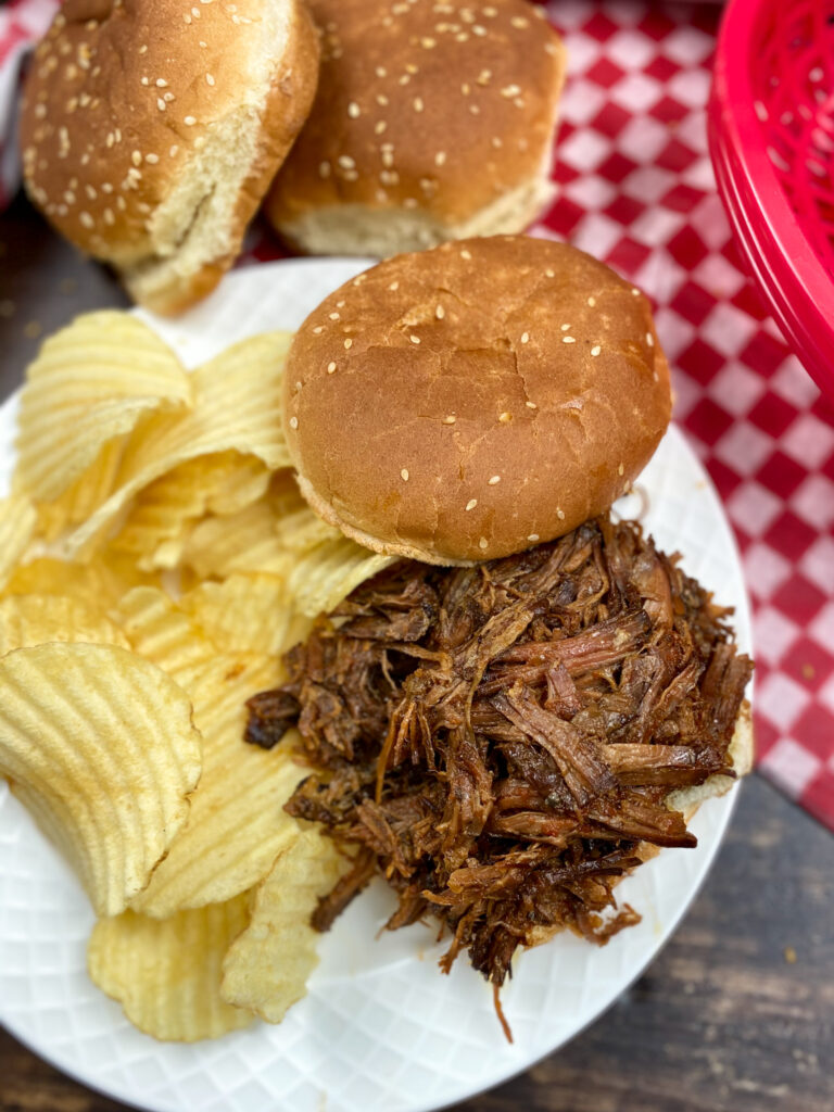 BBQ Sandwich on a white plate with chips.