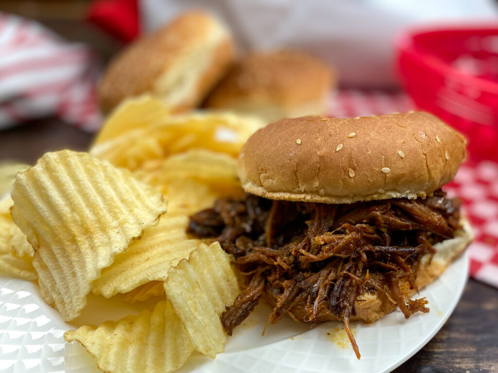 Slow cooker BBQ beef on a plate with chips.