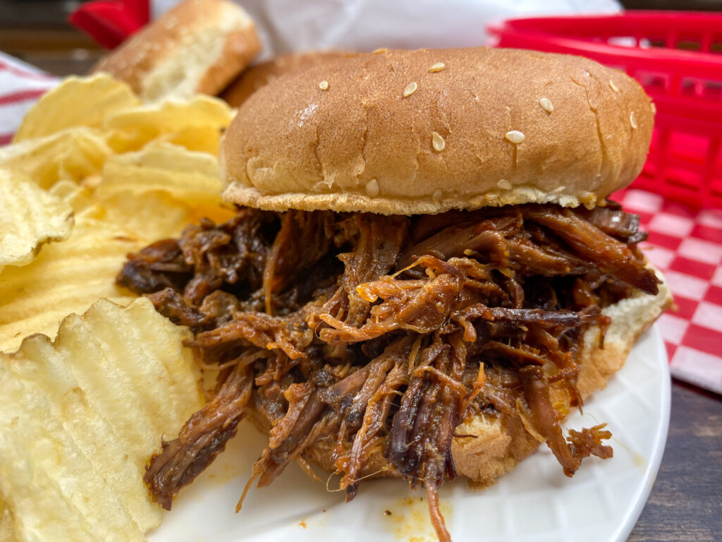 BBQ beef on a sesame seed bun with chips.