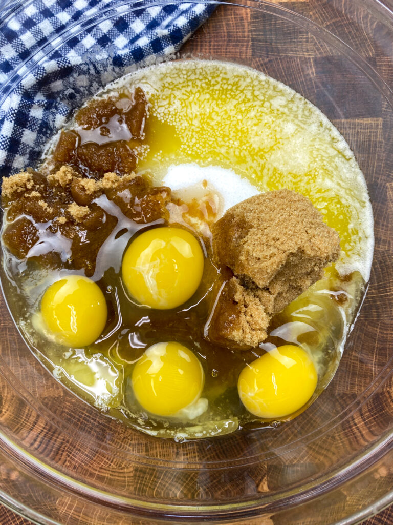 Eggs, sugar, butter, and oil in a large glass bowl.