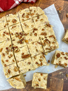 Butter pecan fudge cut into pieces on parchment paper.