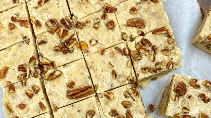 Butter pecan fudge cut into pieces on parchment paper.