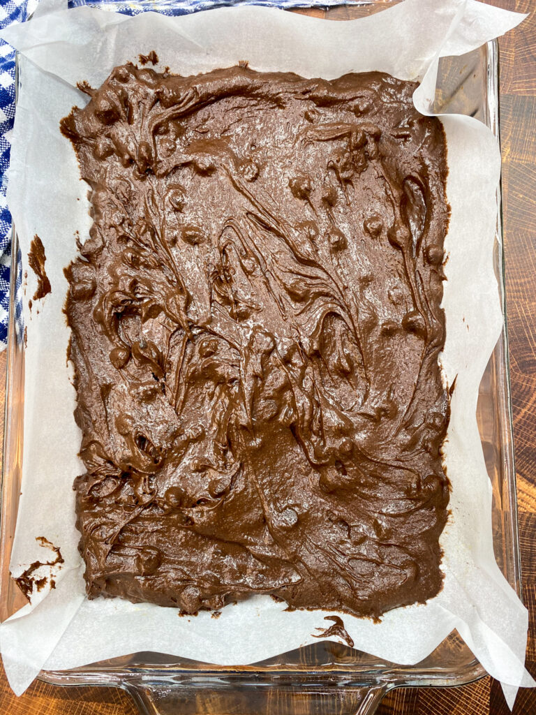 Half of the brownie batter spread into a baking dish.