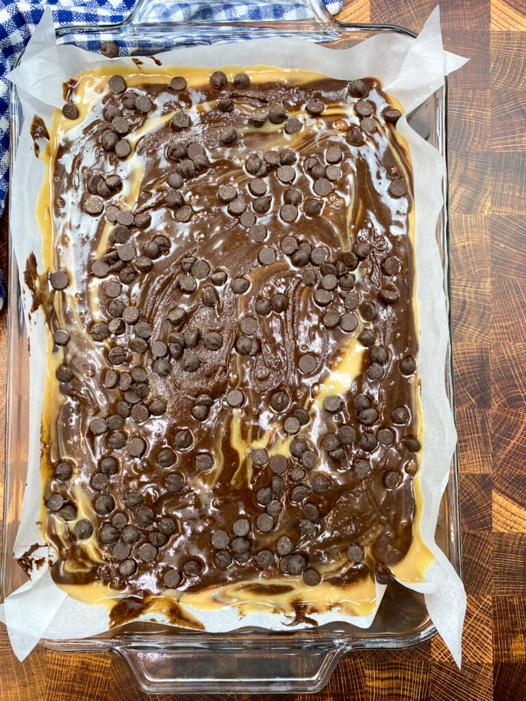 Brownie batter and chocolate chips on top of the caramel mixture in a baking dish.