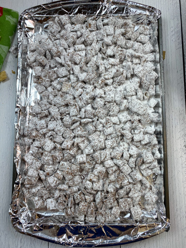 Reindeer chow spread out on a cookie sheet.