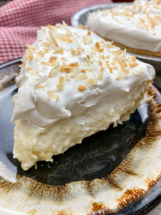 A slice of coconut cream pie on a plate.