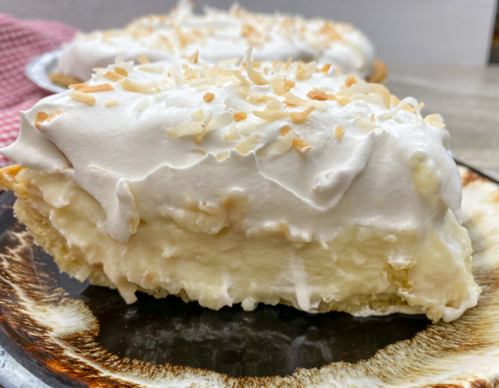 A slice of coconut cream pie recipe on a brown plate.