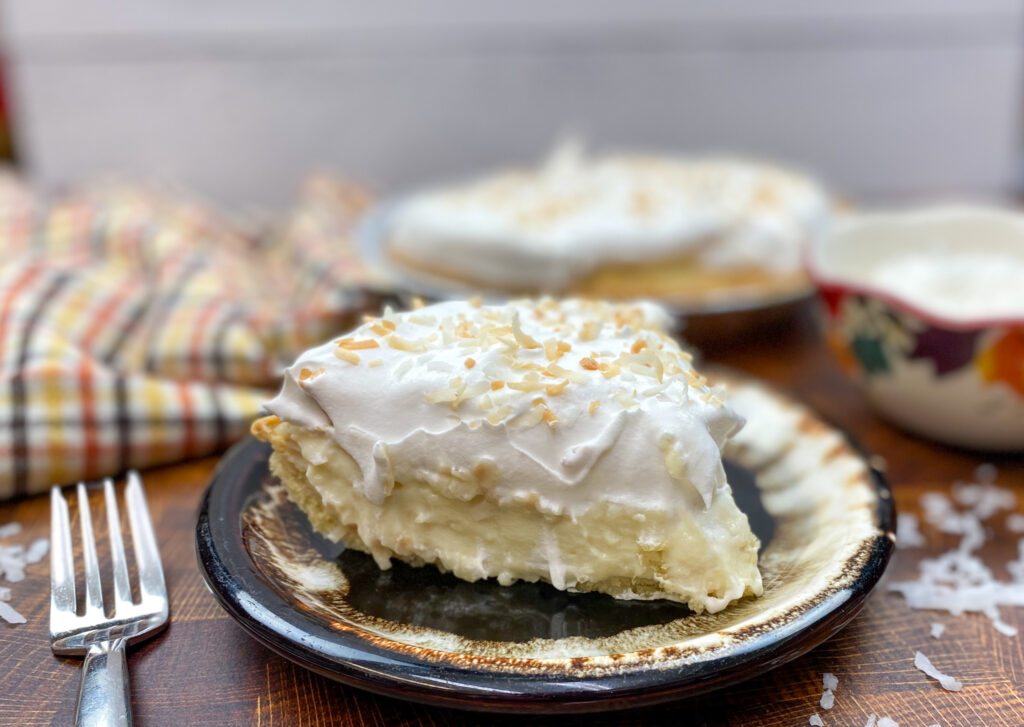 Coconut cream pie on a brown plate.