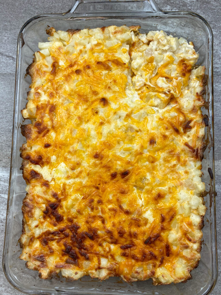 Baked potato cheesy casserole in a baking dish.