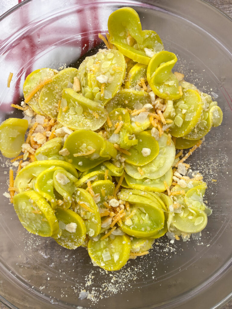 Squash and onions in a bowl with crumbled crackers and cheese.