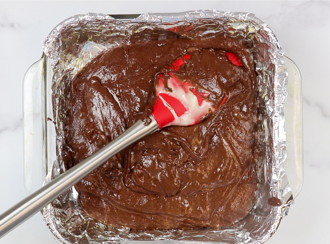 Frosting fudge in a pan with a spatula
