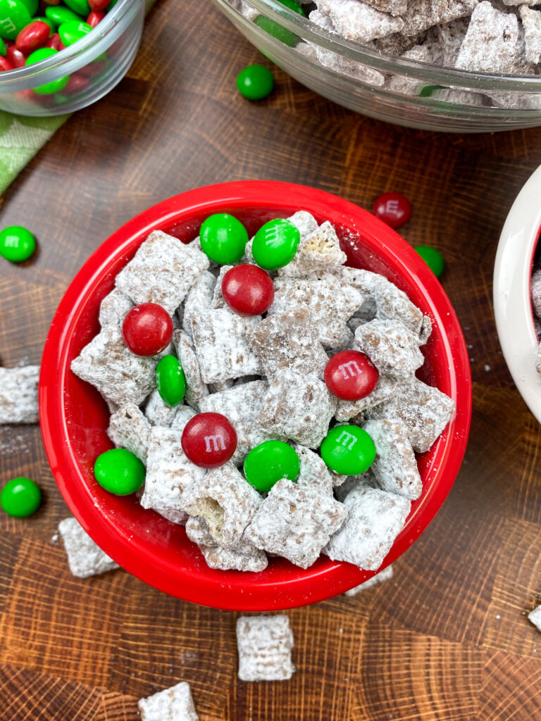 Puppy chow in a red bowl with M&M's.