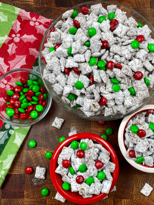 Christmas puppy chow in red and white bowls.