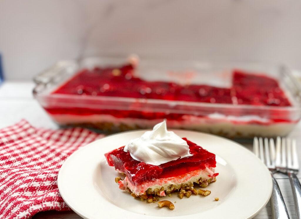 Raspberry Jello dessert on a white plate.