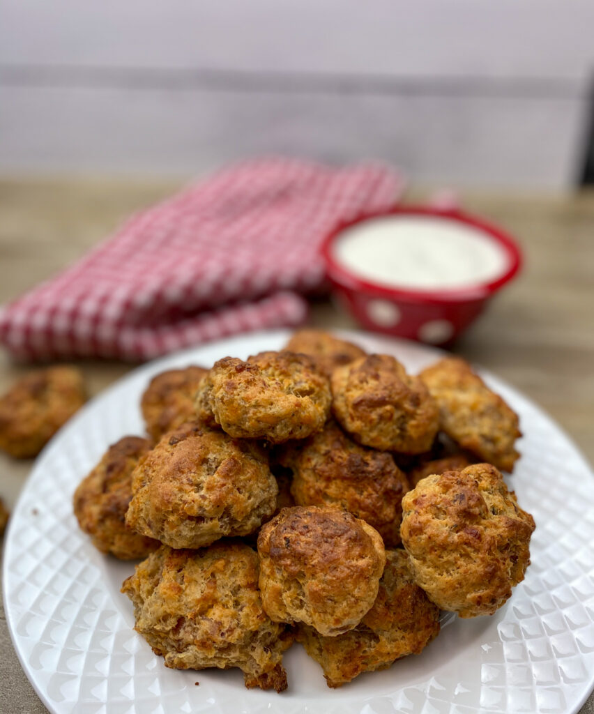 Sausage balls with cream cheese on a white plate.