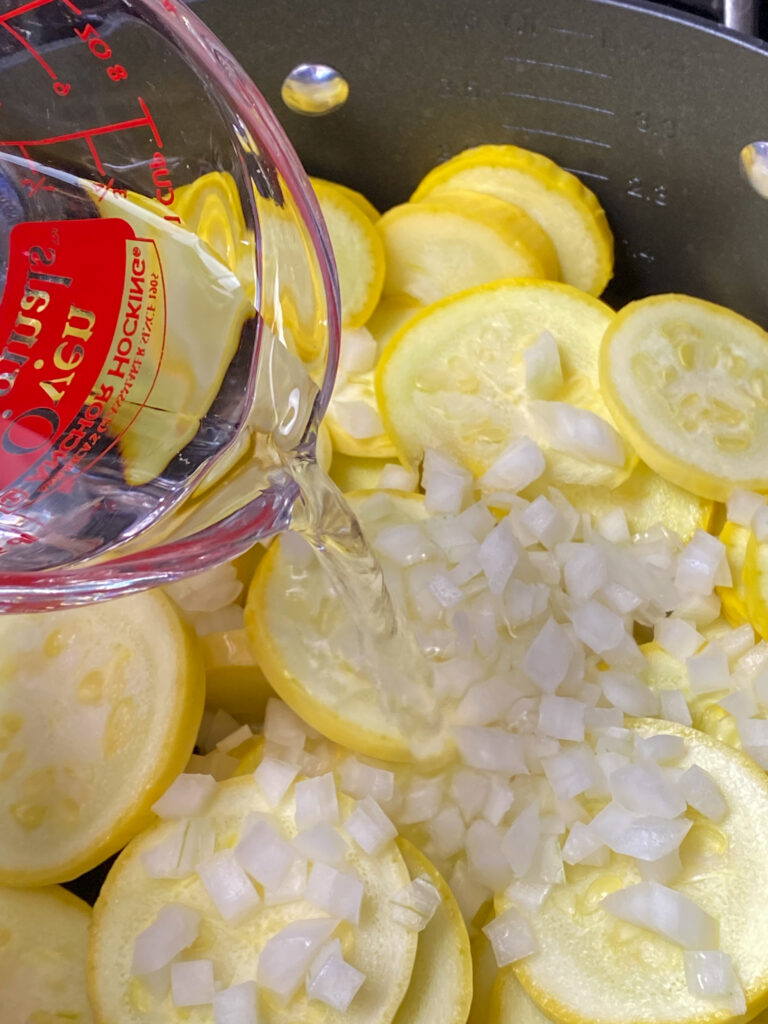 Pouring water over yellow squash and diced onions
