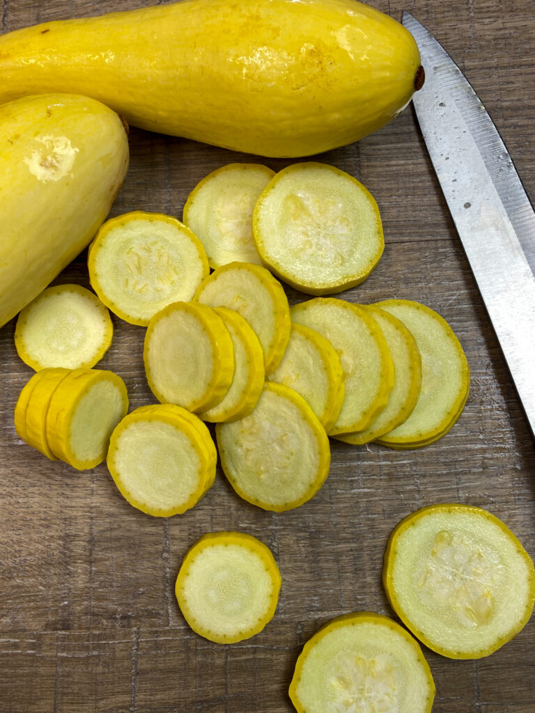 Cutting up yellow squash on the counter.