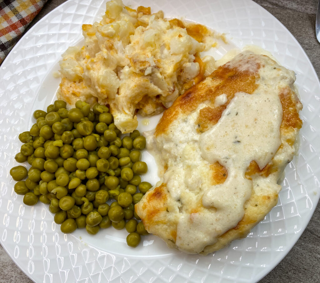Baked chicken dinner on a plate with peas and potatoes.
