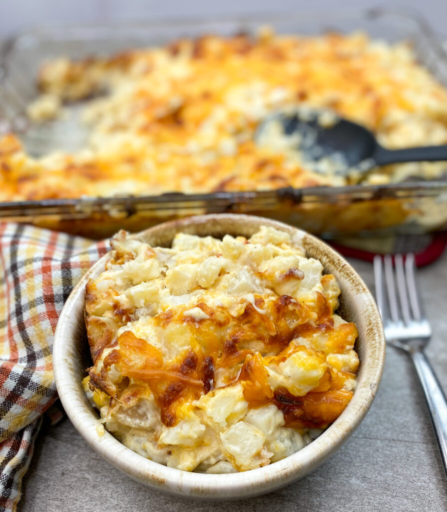 Cheesy potato casserole in a bowl on the counter.
