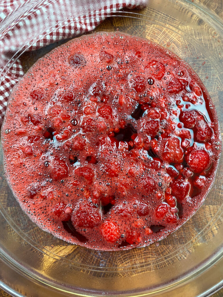 Jello and raspberries in a glass bowl.