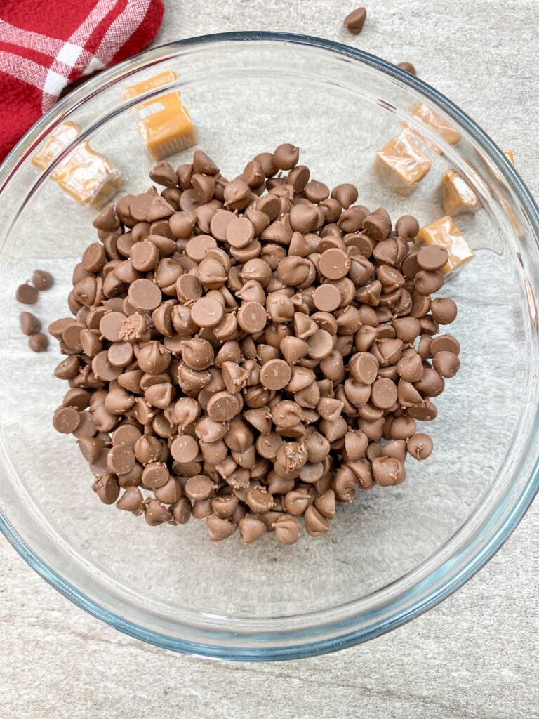 Milk chocolate chips in a small glass bowl.