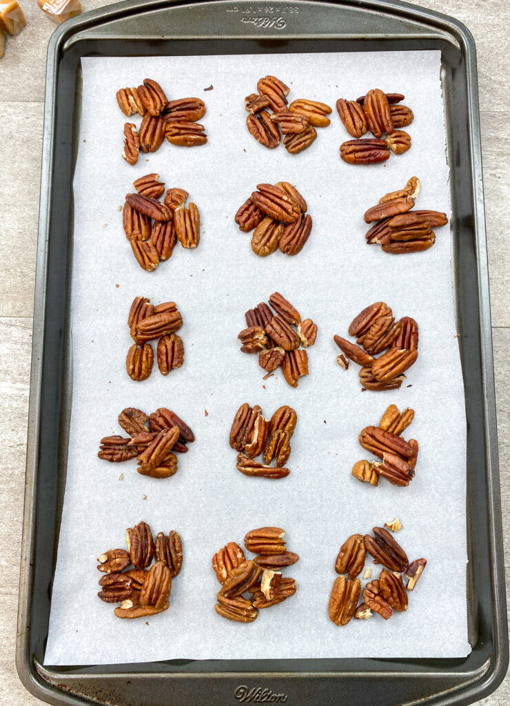 Toasted pecans on a cookie sheet with parchment paper.
