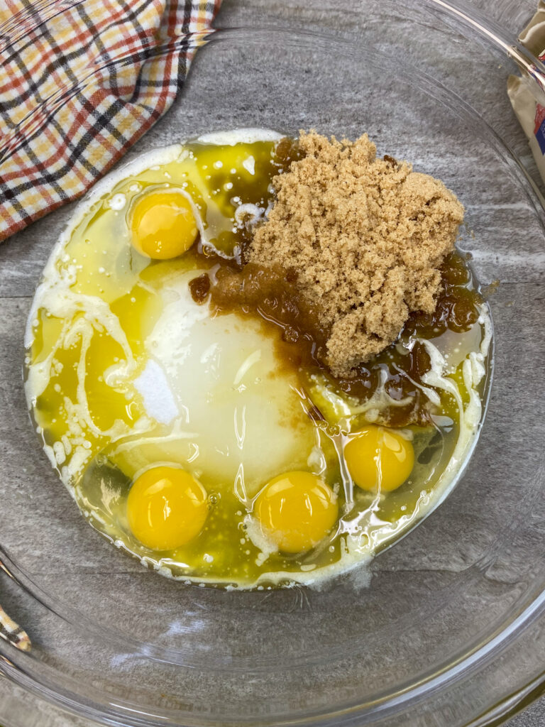 Eggs, sugar, oil, butter, and cocoa in a large glass bowl.