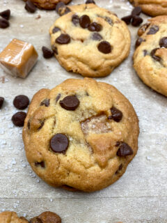 Chocolate chip cookies with caramel on a counter.