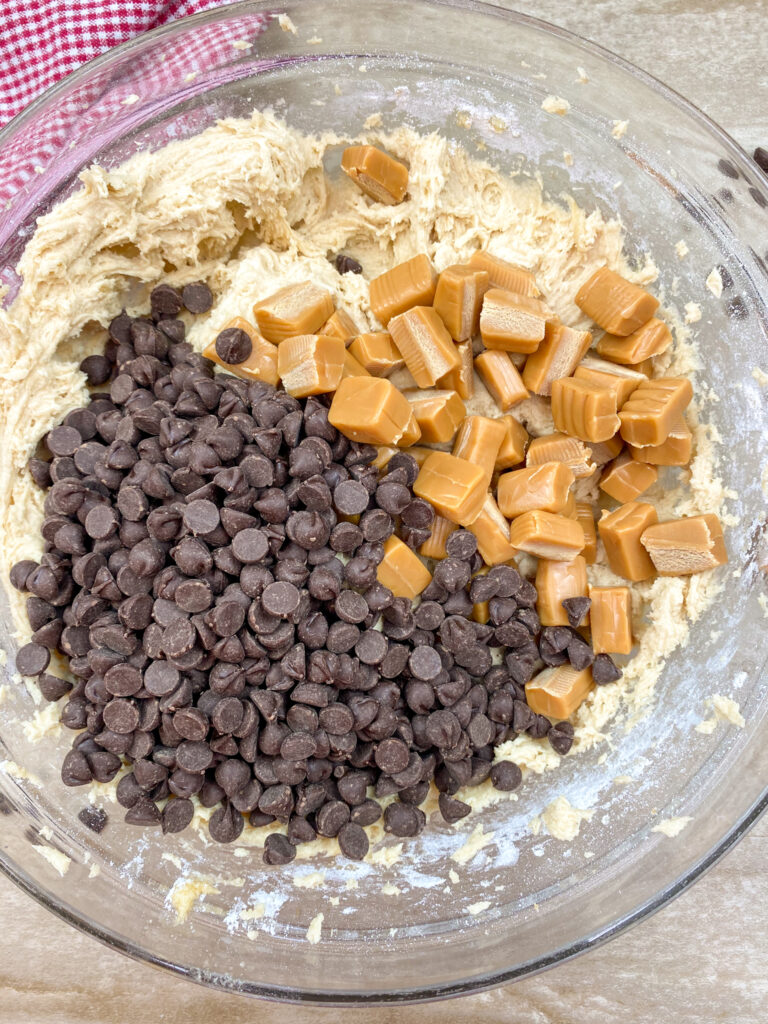 Chocolate chips and caramels in a bowl with cookie batter.