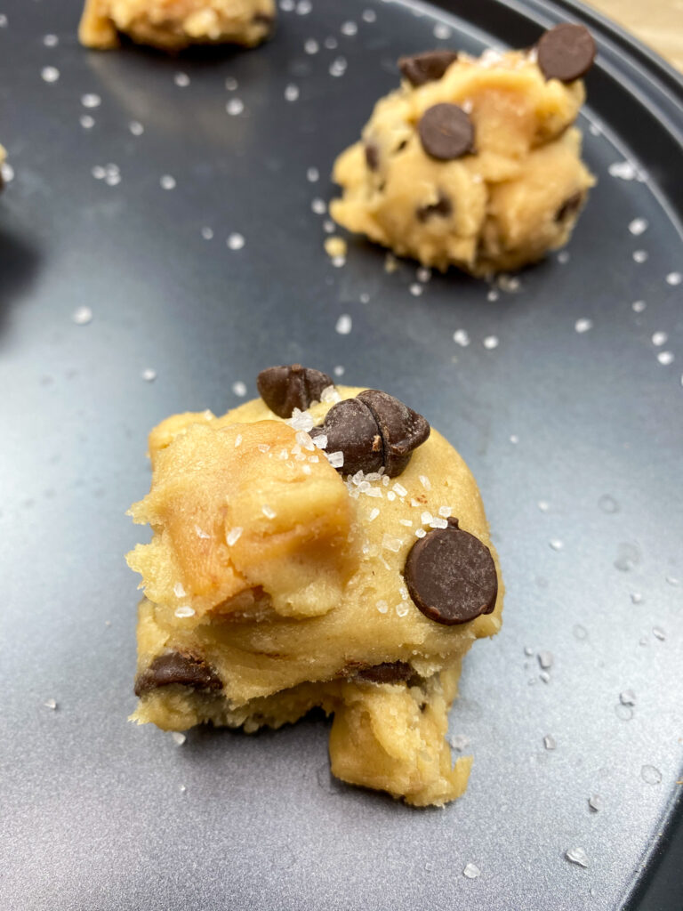 Cookie dough on a cookie sheet with caramels and chocolate chips.