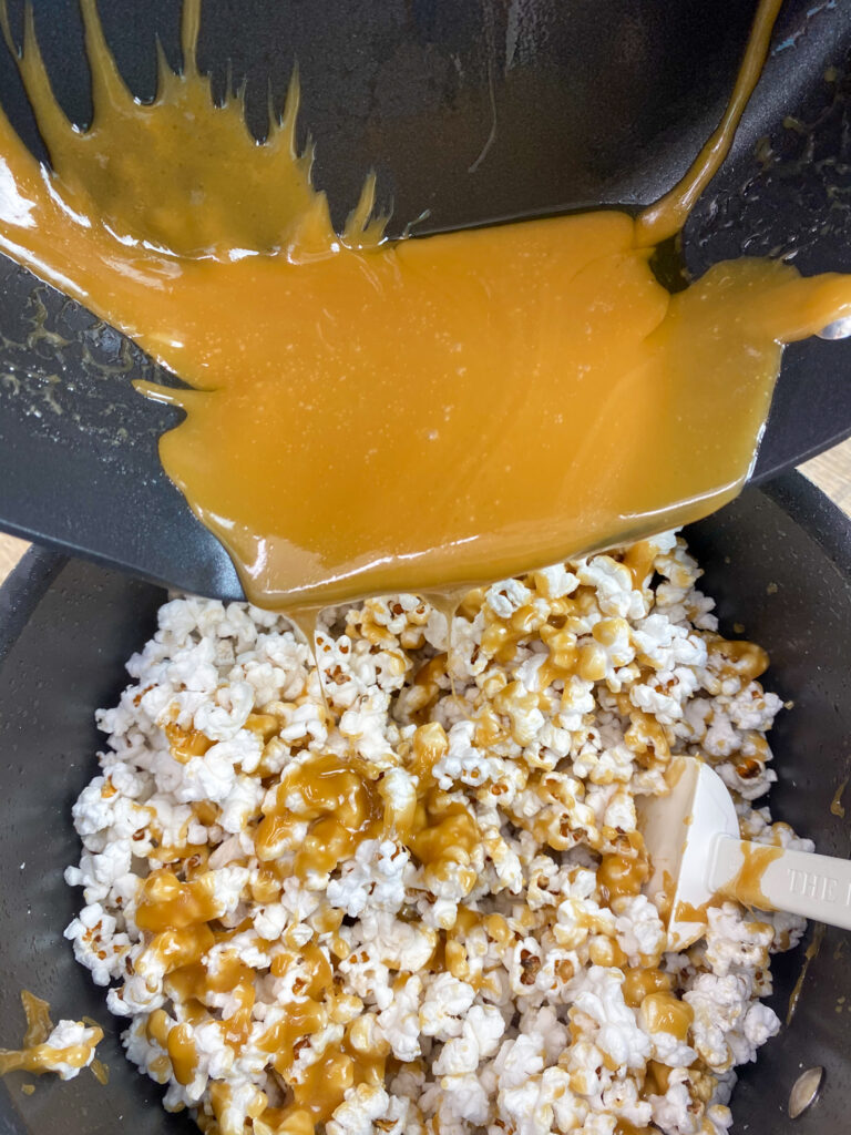 Pouring homemade caramel sauce over popped popcorn.