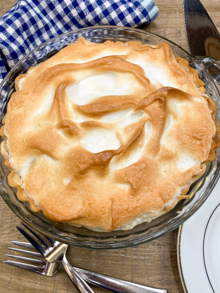 Chocolate pie with meringue in a pie dish sitting on the counter