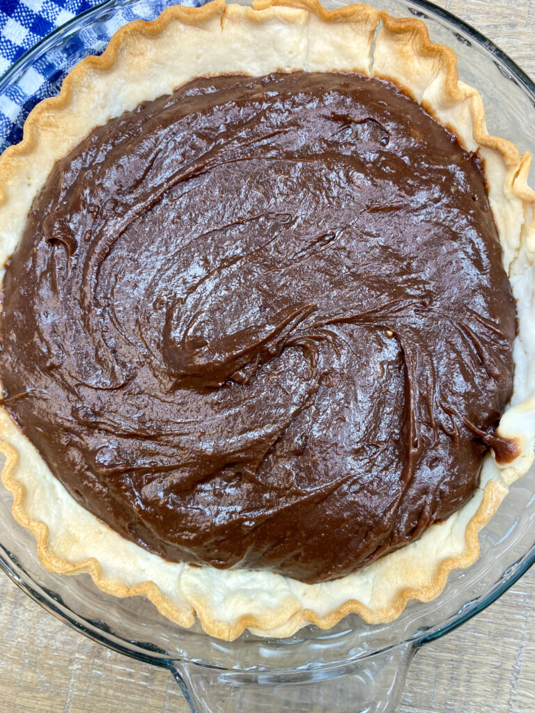 Chocolate pie filling inside of a cooked pie shell.