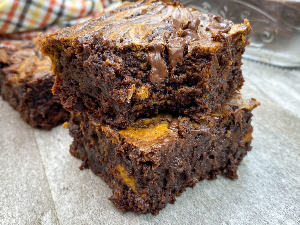 Chocolate cream cheese pumpkin brownies stacked on top of each other.