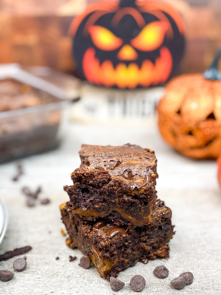 Cream cheese brownies on a counter with Jack-O-Lanterns in the background.