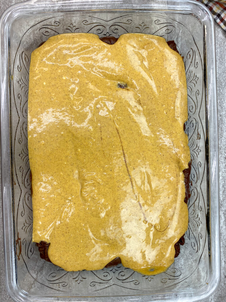 Pumpkin cream cheese mixture spread out over brownies.