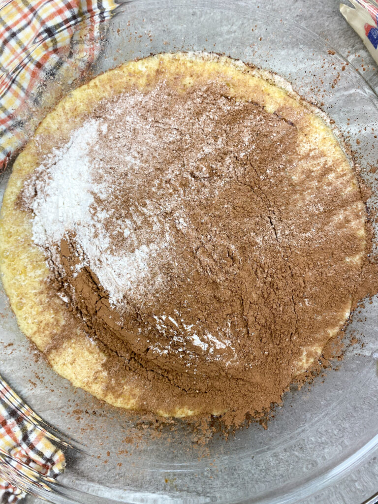 Adding flour and cocoa to a large glass bowl with brownie ingredients.