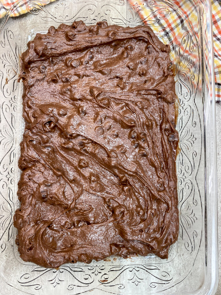"""Brownie batter in a 9"""" x 13"""" glass baking dish."""